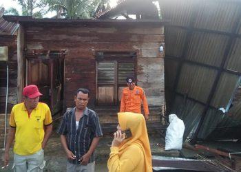 Sejumlah warga berdiri di dekat bangunan rumah yang rusak berat terdampak angin puting beliung Dusun Paulian, Desa Sei Muka, Kecamatan Datuk Tanah Datar, Kabupaten Batubara, Sumatera Utara, Selasa (1/9). FOTO: BPBD Kabupaten Batubara/BNPB