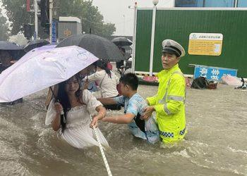Seorang petugas polisi lalu lintas memandu warga menyeberangi jalan yang banjir dengan tali saat hujan deras masih mengguyur di Zhengzhou, Provinsi Henan, China, 20 Juli 2021. FOTO: China Daily via REUTERS