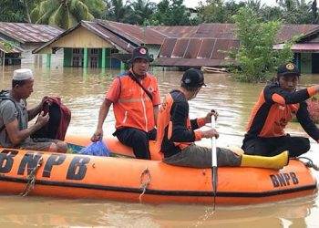 Tim Reaksi Cepat BPBD Kabupaten Paser, Kalimantan Timur, mengevakuasi warga terdampak banjir dengan menggunakan perahu karet. FOTO: BPBD Kabupaten Paser/BNPB